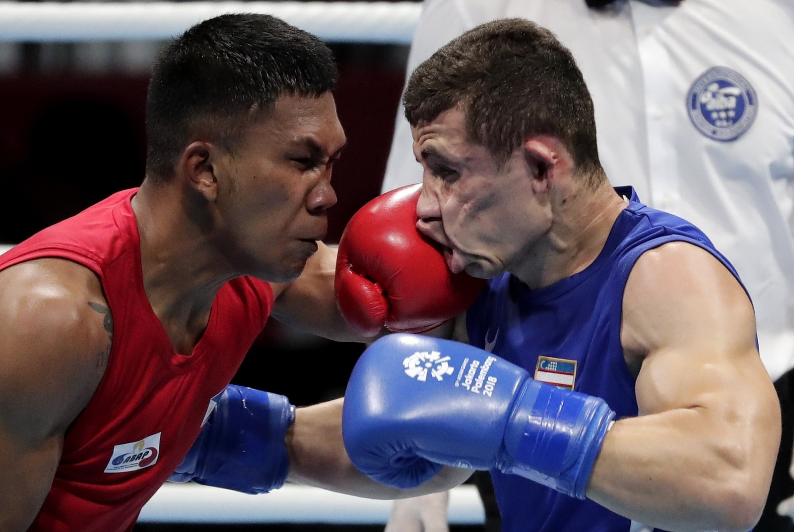 Phillippines' Eumir Felix Marcial, left, lands a blow on the face of Uzbekistan's Israil Madrimov during their men's middleweight boxing semifinal at the 18th Asian Games in Jakarta, Indonesia, on August 31, 2018. (AP Photo/Lee Jin-man)