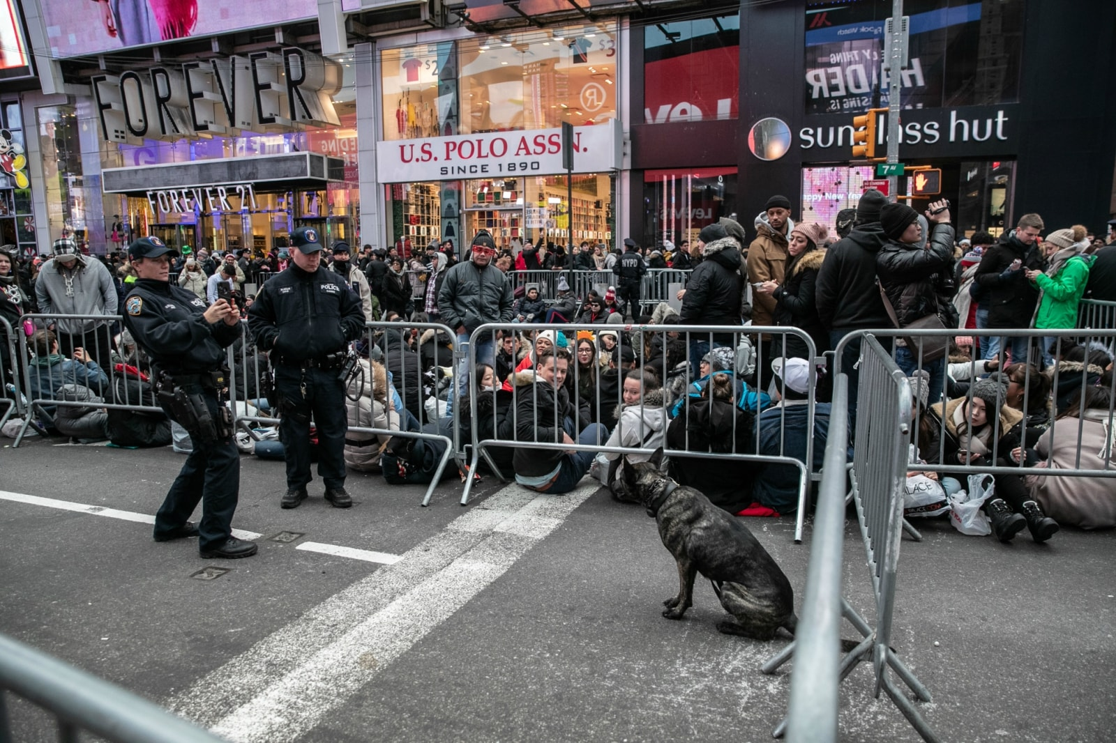 A New York Police Department (NYPD) officer takes a picture of a K-9 dog at Times Square ahead of the New Year's Eve celebrations in Manhattan, New York, US, December 31, 2018. REUTERS/Jeenah Moon