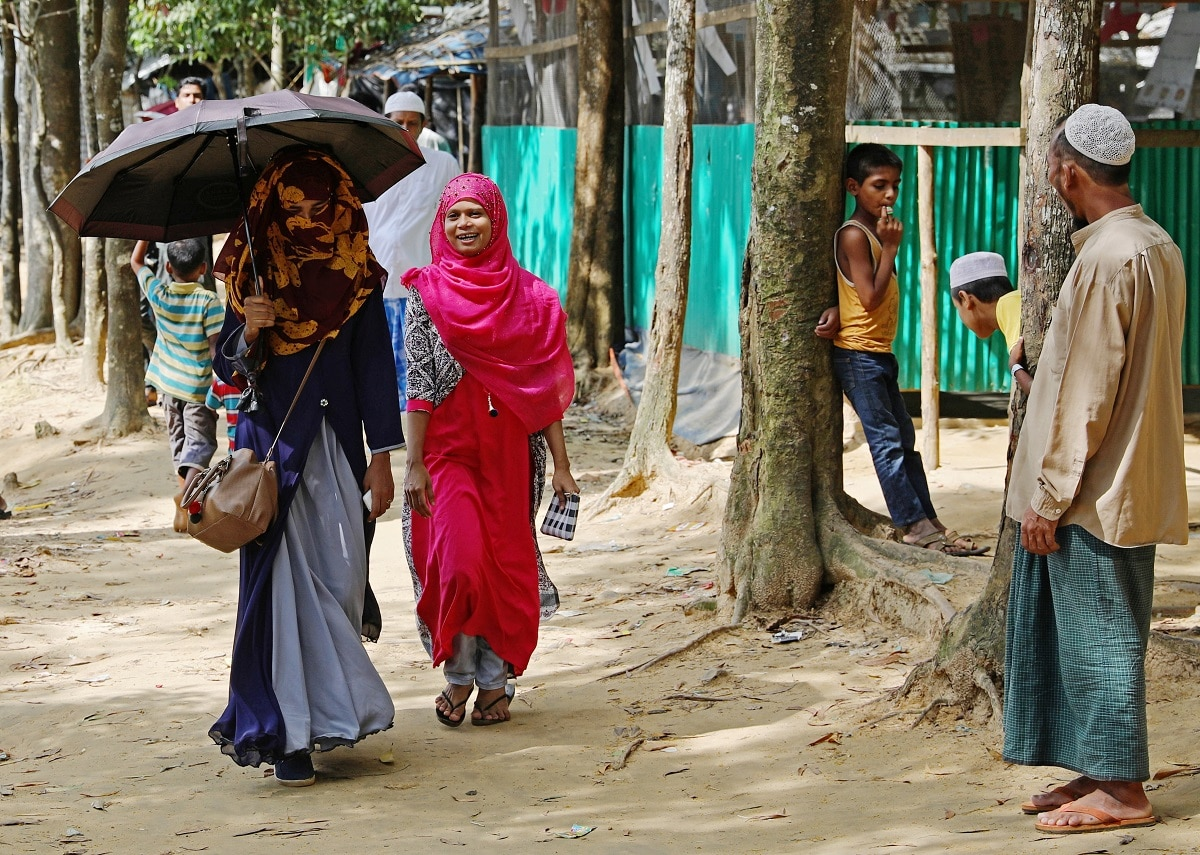 Formin Akter walks with her friend Shahima through a refugee camp as she departs for Chittagong to attend school. (REUTERS/Mohammad Ponir Hossain)