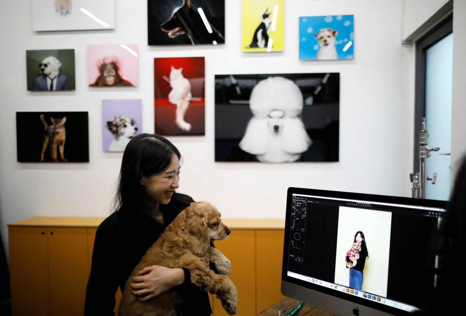 A woman looks at pictures of her and her pet dog at a pet studio in Seoul, South Korea, January 17, 2019. REUTERS/Kim Hong-Ji