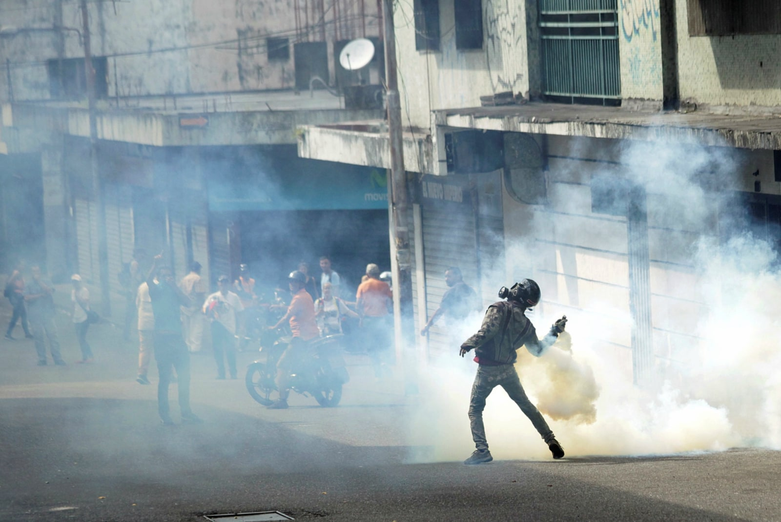 A demonstrator throws back a gas canister while clashing with security forces during a rally against Venezuelan President Nicolas Maduro's government and to commemorate the 61st anniversary of the end of the dictatorship of Marcos Perez Jimenez in Tachira, Venezuela January 23, 2019. REUTERS/Carlos Eduardo Ramirez