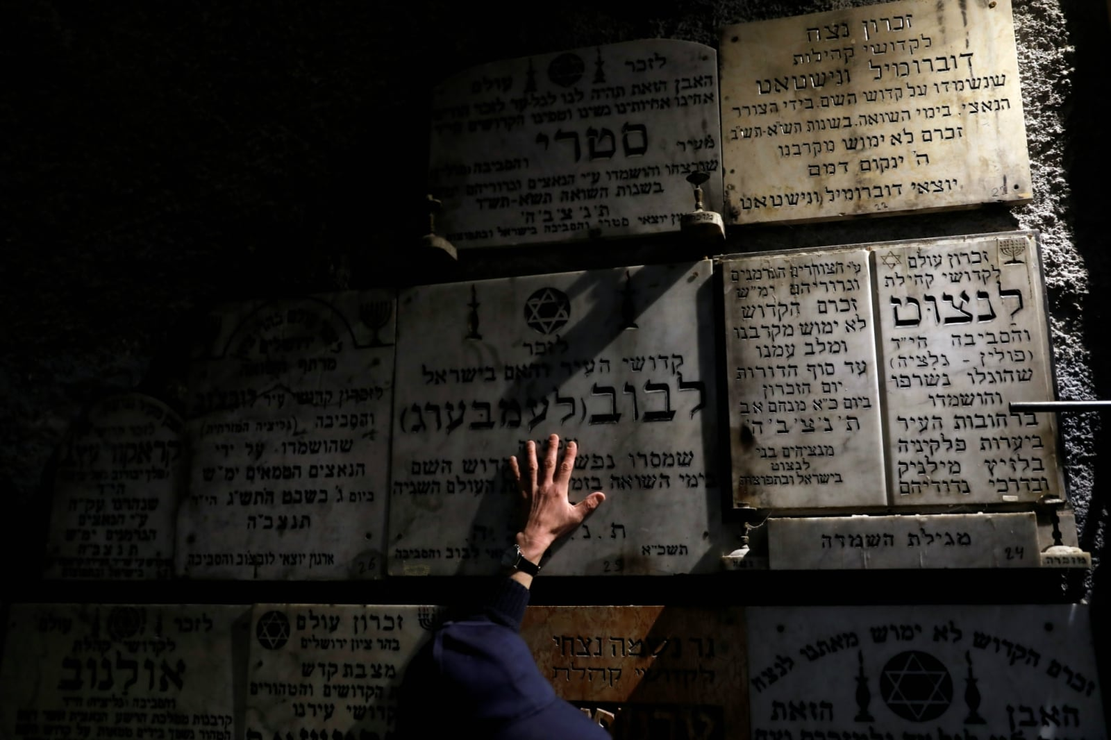 A man touches a gravestone commemorating the Jewish villages and towns whose communities were wiped out by the Nazis, inside