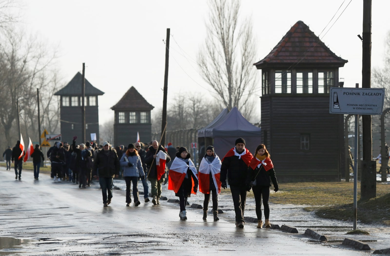 People walk along the fence of the former Nazi German concentration and extermination camp Birkenau, during the ceremonies marking the 74th anniversary of the liberation of the camp and International Holocaust Victims Remembrance Day, near Oswiecim, Poland, January 27, 2019. REUTERS/Kacper Pempel