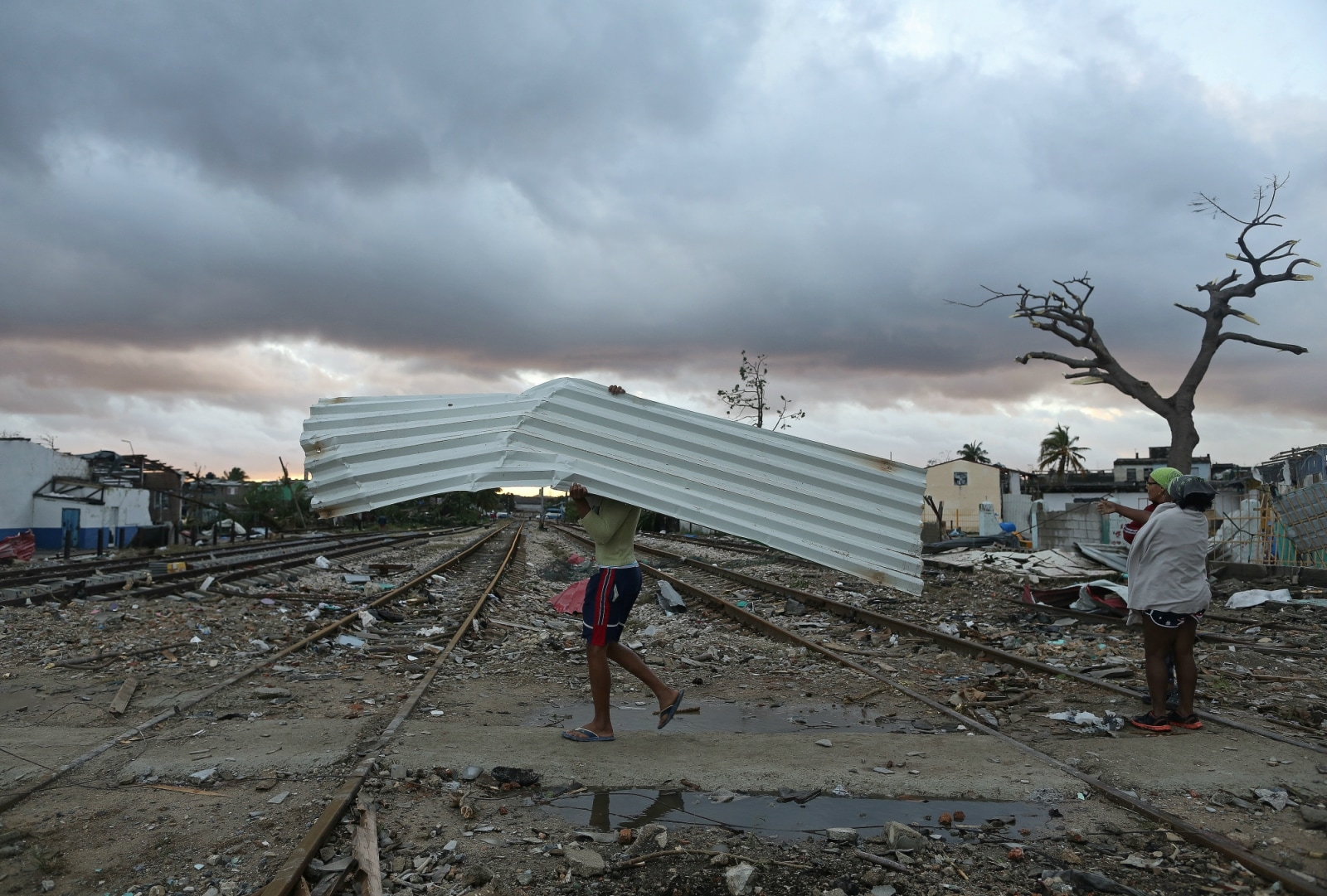 A man carries a sheet of aluminium after a tornado ripped through a neighbourhood in Havana, Cuba January 28, 2019. REUTERS/Fernando Medina