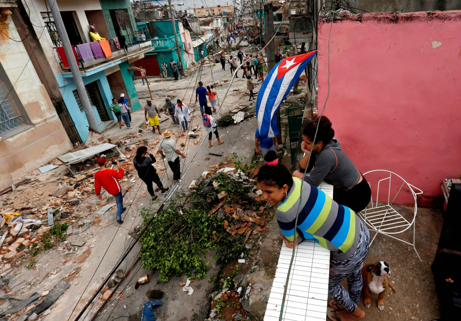 People look on as others walk past debris after a tornado ripped through a neighbourhood in Havana, Cuba January 28, 2019. REUTERS/Stringer