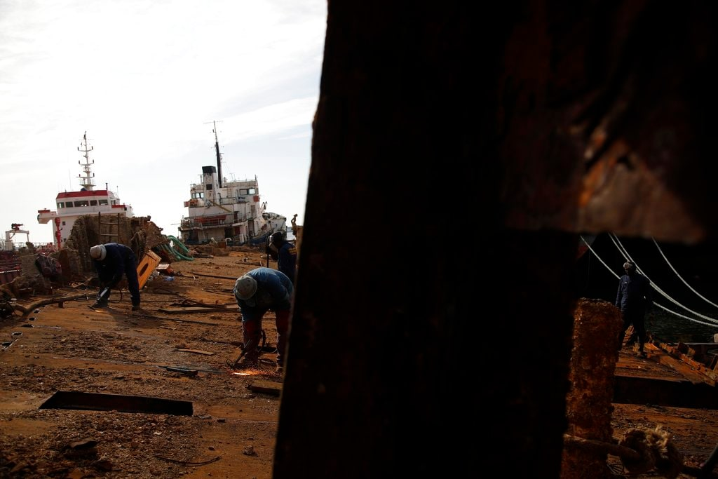 """In this Monday, November 5, 2018 photo, in a shipyard of Perama, west of Athens, workers cut up the rusted remains of a ferry that was recovered after spending years as a shipwreck. One expert calls the abandoned ships """"an environmental bomb.""""(AP Photo/Thanassis Stavrakis)"""