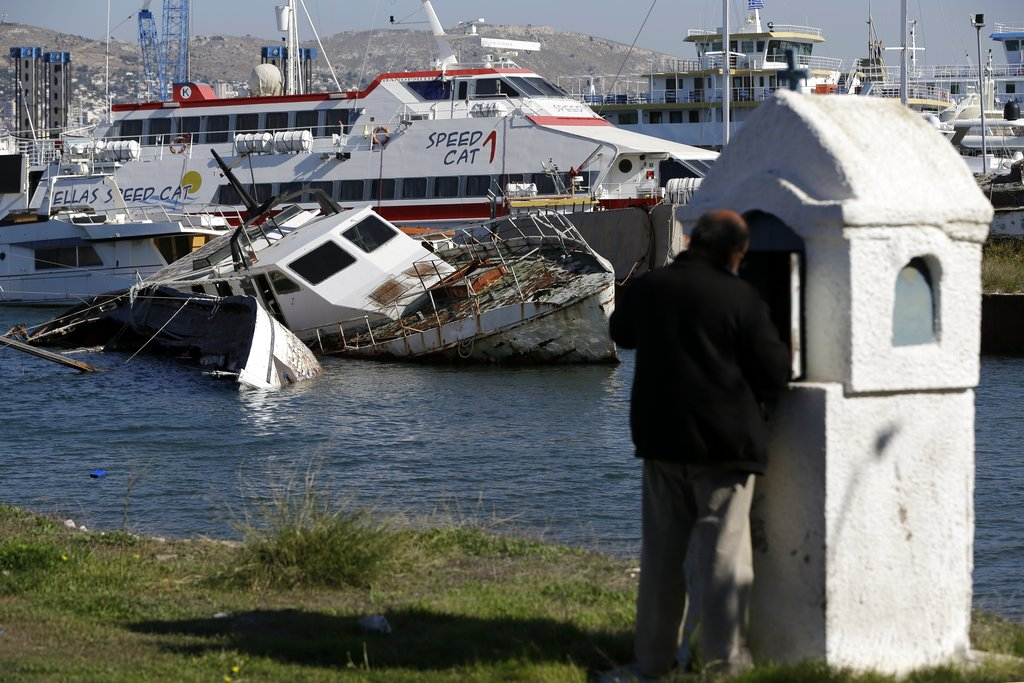 In this Tuesday, November 6, 2018 photo, a half sunken small boat is photographed near a shipyard in Salamina island, west of Athens as a man lights a candle at a roadside shrine. (AP Photo/Thanassis Stavrakis)