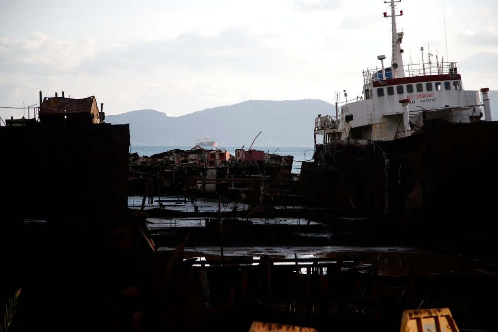 """In this Wednesday, December 19, 2018 photo, a cut tanker with crude oil, that was recovered after spending years as a shipwreck is photographed at a dock in Elefsina, west of Athens. One expert calls the abandoned ships """"an environmental bomb."""" (AP Photo/Thanassis Stavrakis)"""