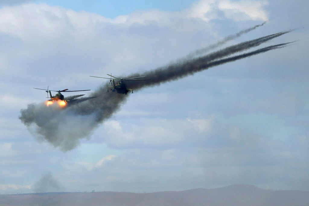 In this Thursday, September 13, 2018 file photo, military helicopters fire weapons about 250 kilometers (156 miles) north of the city of Chita during the Vostok military exercises in Eastern Siberia, Russia. The week-long maneuvers span vast expanses of Siberia and the Far East, the Arctic and the Pacific Oceans. They involve nearly 300,000 Russian troops along with 1,000 Russian aircraft and 36,000 tanks and other combat vehicles. (AP Photo/Sergei Grits)