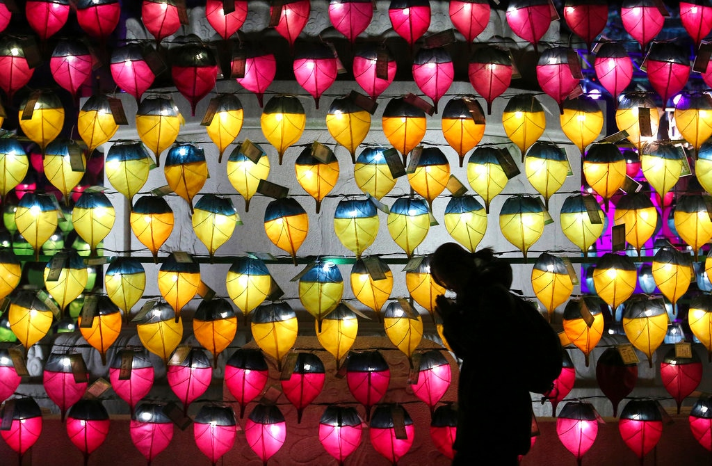 A woman prays in front of a wall of lanterns to celebrate the New Year at the Jogyesa Buddhist temple in Seoul, South Korea, Monday, December 31, 2018. (AP Photo/Ahn Young-joon)
