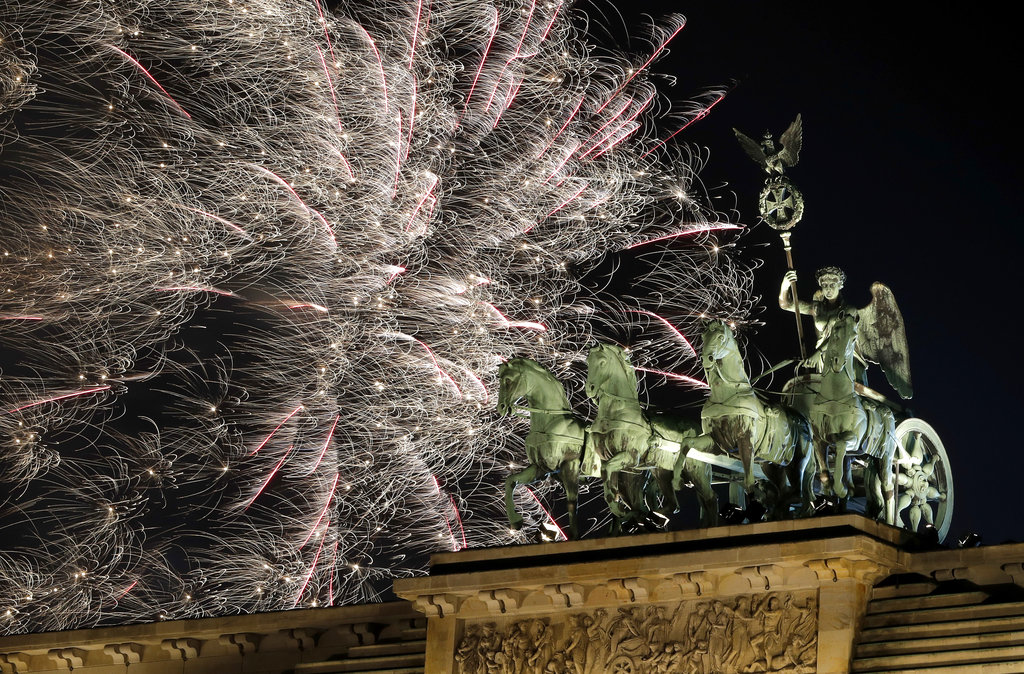 Fireworks light the sky above the Quadriga at the Brandenburg Gate shortly after midnight in Berlin, Germany, Tuesday, January 1, 2019. Hundred thousands of people celebrated New Year's Eve welcoming the new year 2019 in Germany's capital. (AP Photo/Michael Sohn)