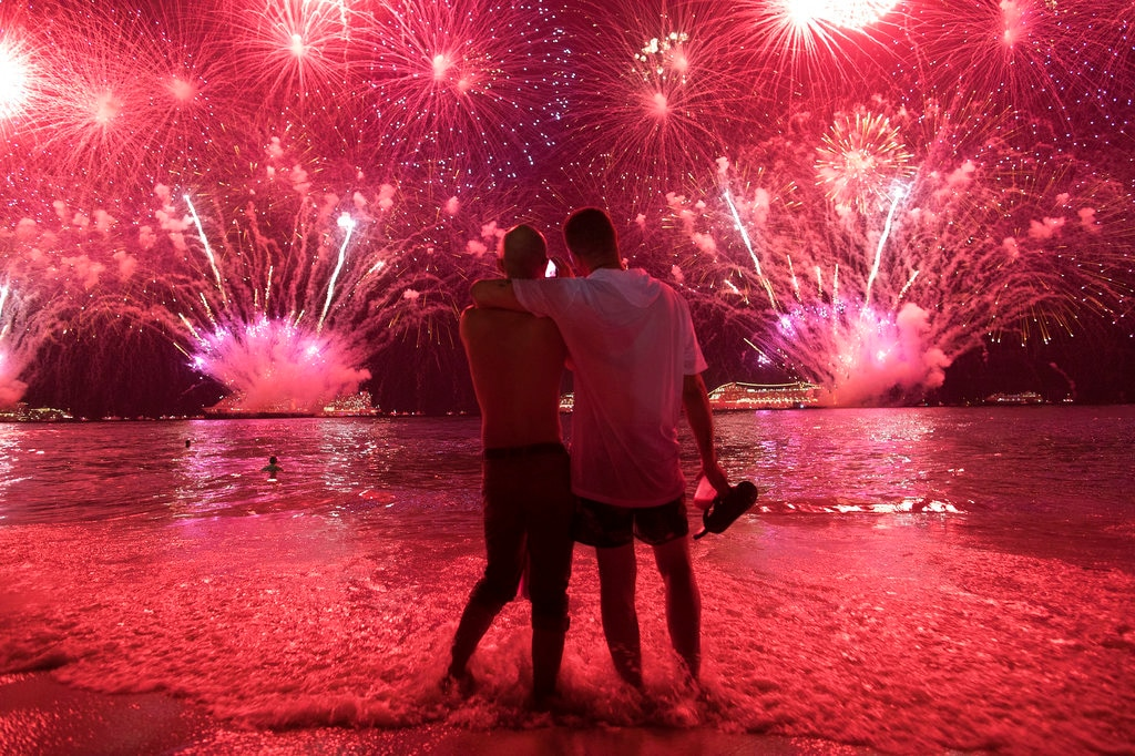 Two men watch the fireworks exploding over Copacabana Beach during the New Year's celebrations in Rio de Janeiro, Brazil, Tuesday, January 1, 2019. (AP Photo/Leo Correa)