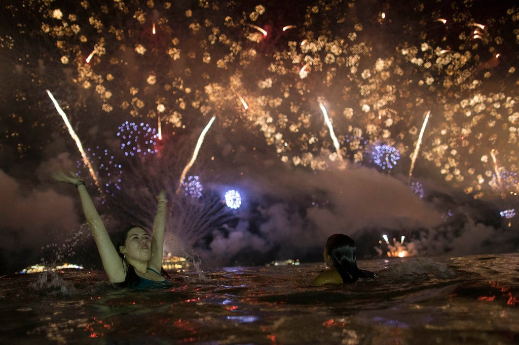 A woman watches the fireworks exploding over Copacabana Beach during the New Year's celebrations in Rio de Janeiro, Brazil, Tuesday, January 1, 2019. (AP Photo/Leo Correa)
