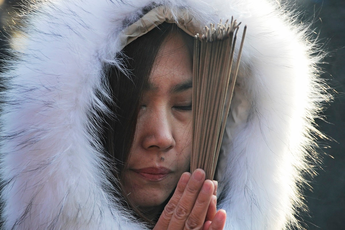 A woman holds incense and prays for health and fortune on the first day of the New Year at Yonghegong Lama Temple in Beijing. (AP Photo/Andy Wong, File)