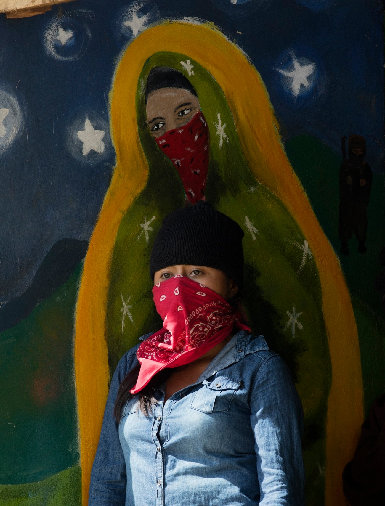 A masked, female member of the Zapatista National Liberation Army, EZLN, stands by a mural depicting a masked version of the Virgin of Guadalupe, during an event marking the 25th anniversary of the Zapatista uprising in La Realidad, Chiapas, Mexico. Mexico's leftist Zapatistas have continued their aggressive criticism of the country's new president, accusing Andres Manuel Lopez Obrador of dishonesty and vowing to confront him. (AP Photo/Eduardo Verdugo)