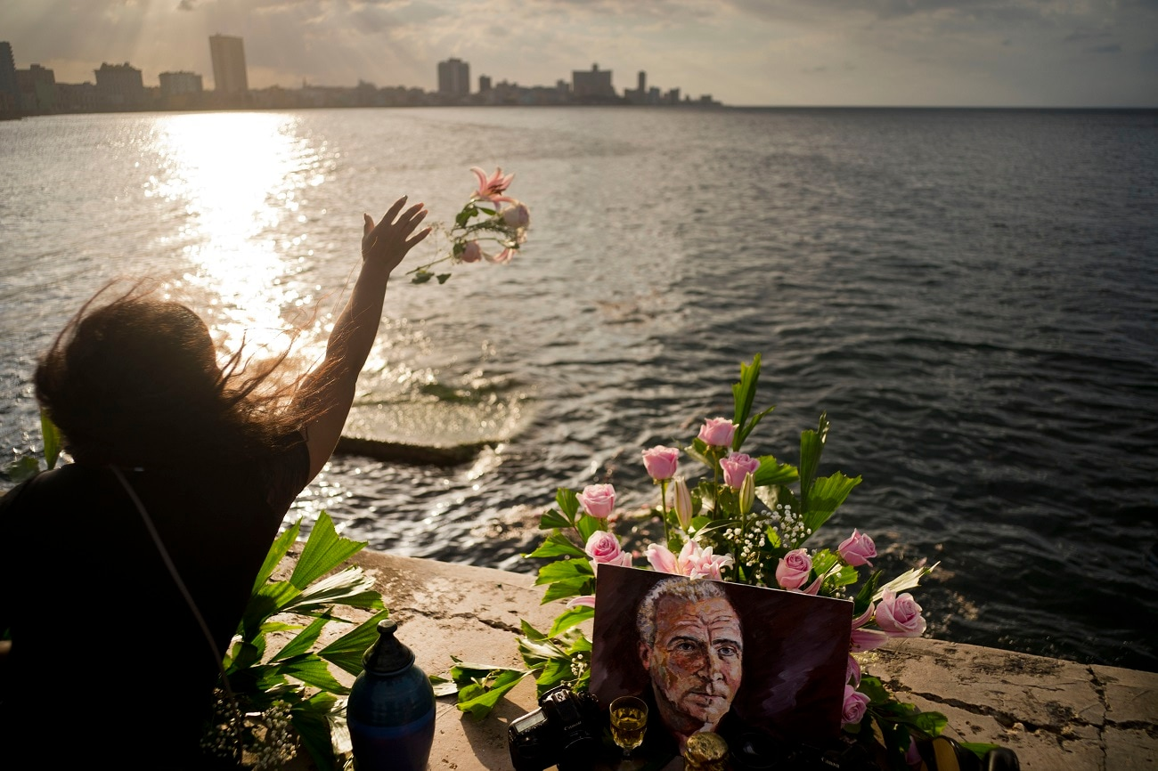 A person throws flowers into the sea during a memorial service for late photojournalist Desmond Boylan, from the Malecon promenade where some of his ashes were also scattered into the water at sunset in Havana, Cuba. Boylan, a photographer who covered war and conflict across the world before dedicating his life to documenting the daily joys and tribulations of life in Cuba for The Associated Press, died suddenly while on assignment. (AP Photo/Ramon Espinosa)