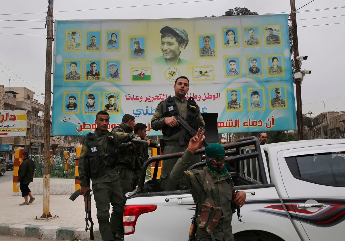 Kurdish internal security forces stand on their vehicle in front of a giant poster showing portraits of fighters killed fighting against the Islamic State group, in Manbij, north Syria.  (AP Photo/Hussein Malla, File)