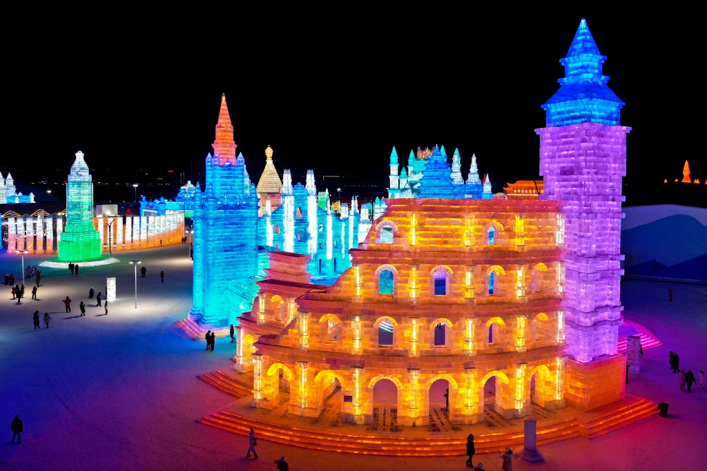An aerial view taken with a drone shows visitors tour colorful Colosseum of Rome made from blocks of ice at the Harbin International Ice and Snow festival held in Harbin in northeastern's China's Heilongjiang province, Friday, January 4, 2019. (AP Photo/Olivia Zhang)