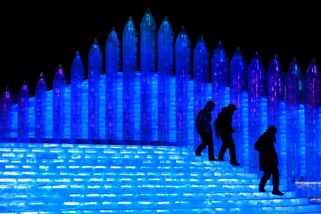 Visitors walk by structures made from blocks of ice at the Harbin International Ice and Snow festival held in Harbin in northeastern's China's Heilongjiang province. (Chinatopix via AP)