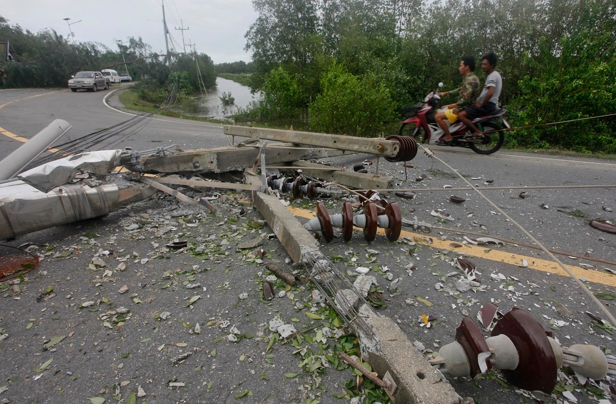 Thai men ride a motorbike avoiding toppled power lines in the aftermath of Tropical Storm Pabuk.(AP Photo/Sumeth Panpetch)