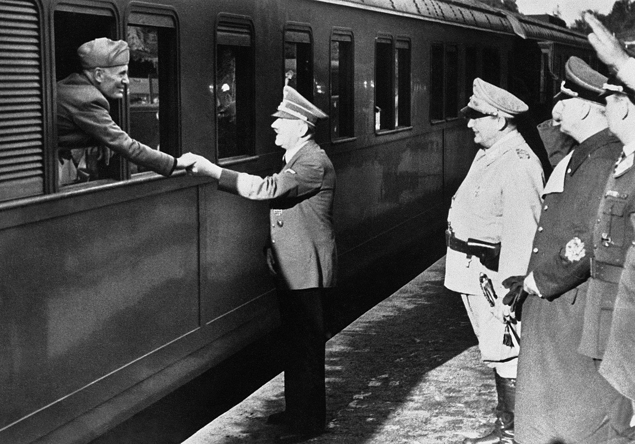 German Chancellor Adolf Hitler gives Italian dictator Benito Mussolini a left-handed shake as he leaves by train after a conference in Germany. At right is Foreign Minister Joachim Von Ribbentrop and Reich Marshal Herman Goering, second right. (AP Photo)