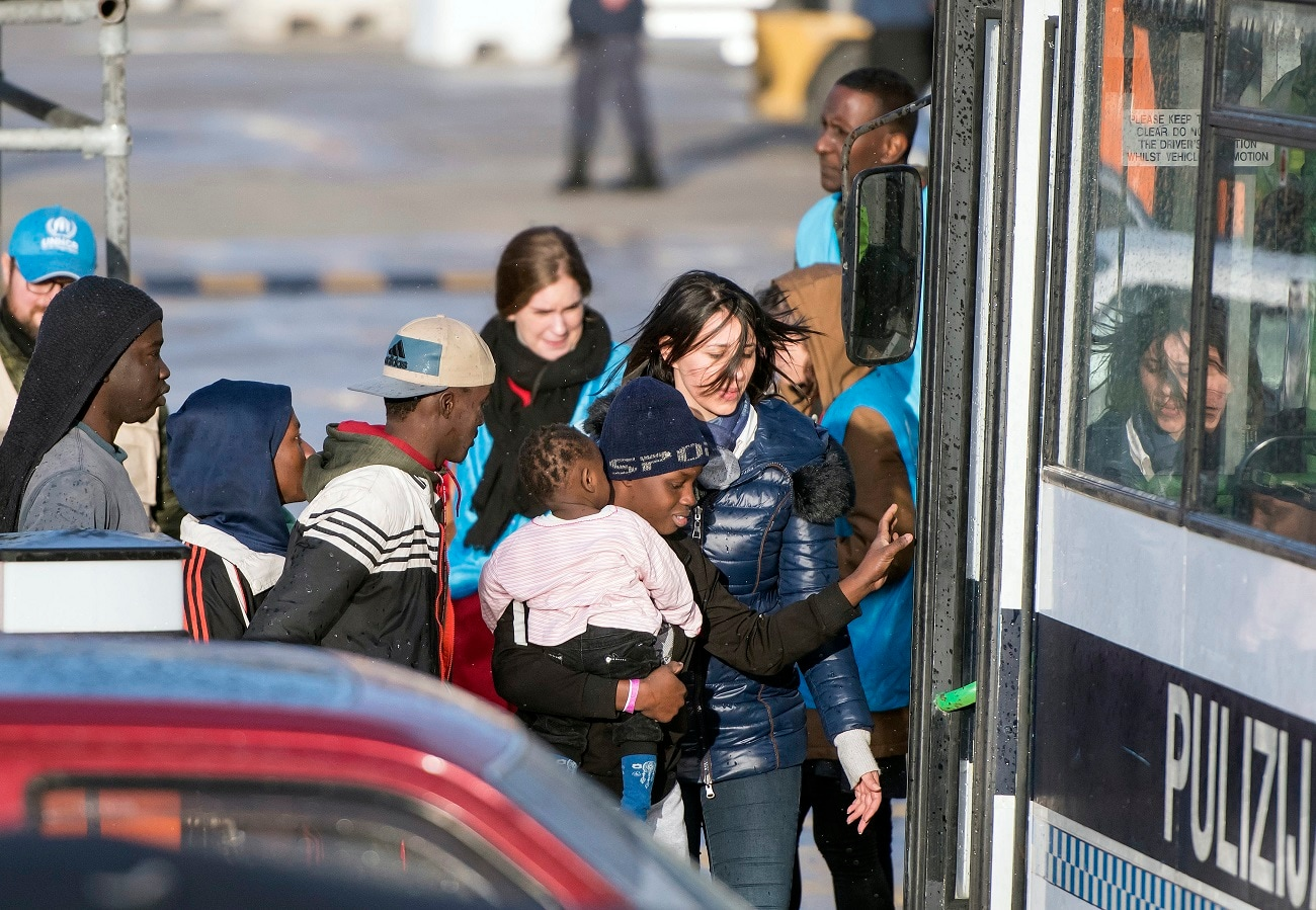 Migrants board a bus after disembarking at Hay Wharf, Pieta, Malta. (AP Photo/Rene Rossignaud)
