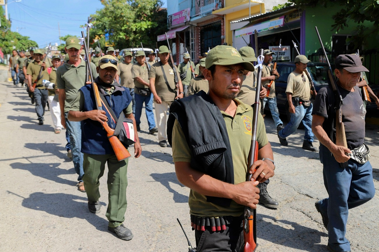 Members of volunteer police force walk the streets during a march to raise awareness of local issues in Copala, Guerrero state, Mexico. Marking the sixth anniversary of the founding of the Union of Towns and Organizations of the State of Guerrero, UPOEG, their main goal is to provide security for the locals who fear the rise in violence due to cartel activity. (AP Photo/Bernandino Hernandez)