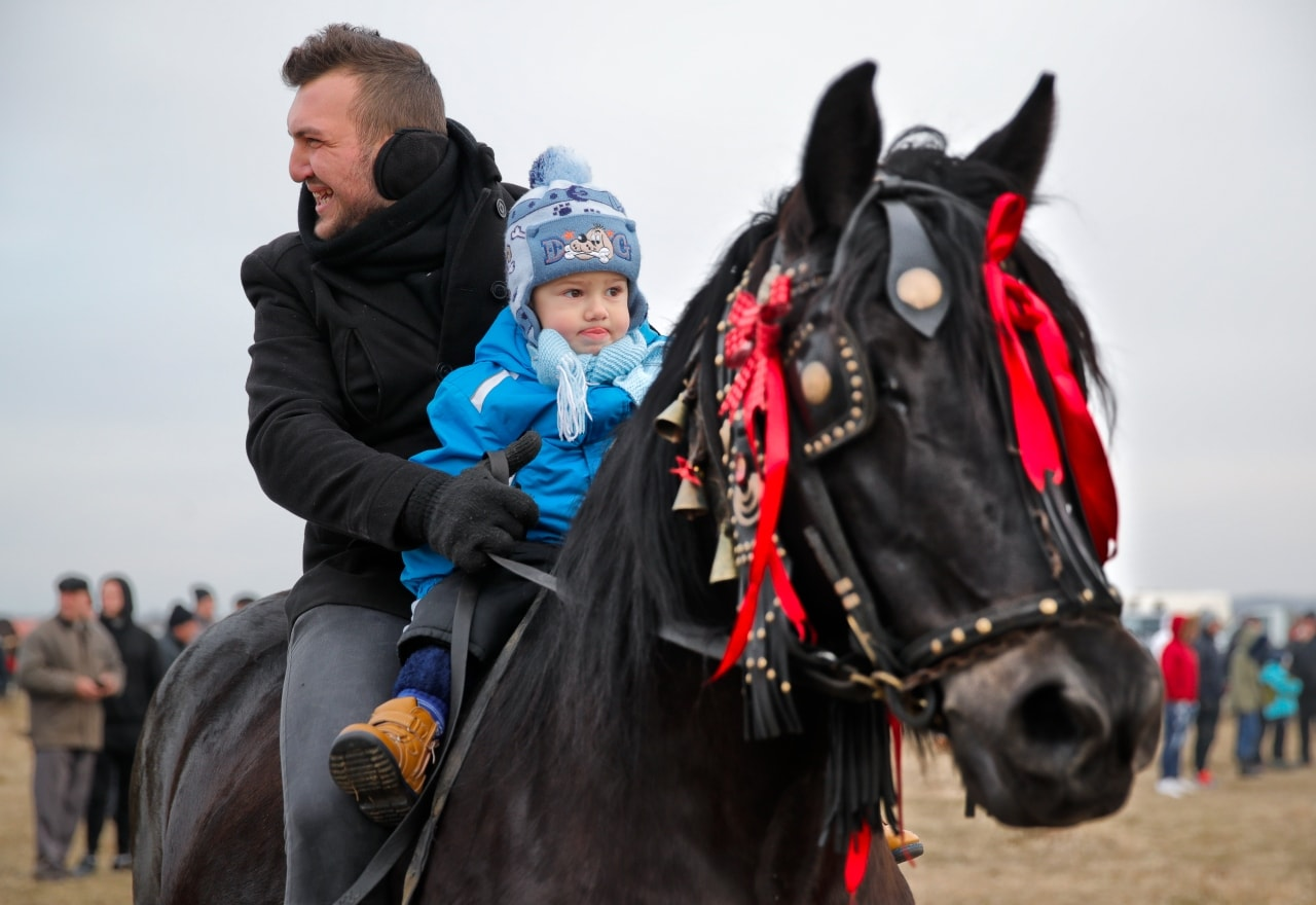 In this Sunday, Jan. 6, 2019, photograph a man rides a horse along with a baby during Epiphany celebrations in Pietrosani, Romania.