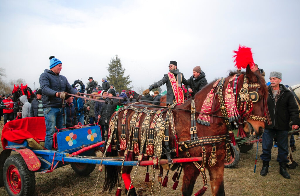 In this Sunday, Jan. 6, 2019, photograph an Orthodox priest sprinkles holy water on horses and people during Epiphany celebrations in Pietrosani, Romania. Epiphany celebrations bring together hundreds of people in the Romanian village of Pietrosani for a day out in freezing temperatures that culminates in a bareback horse race across muddy, frozen or snowy fields.