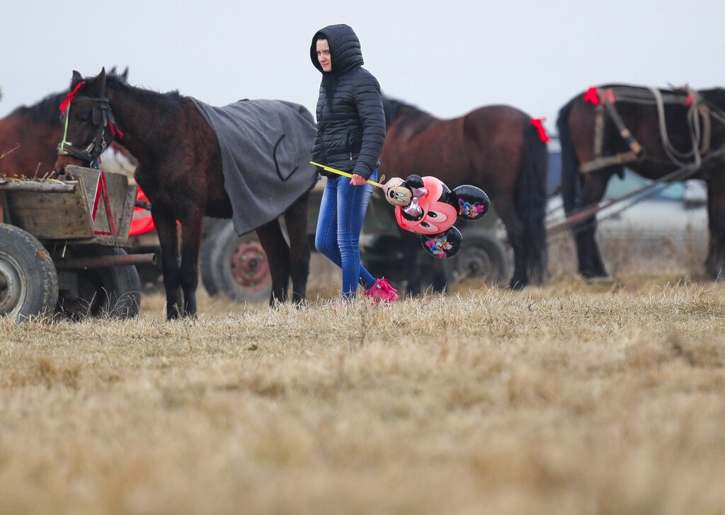 In this Sunday, Jan. 6, 2019, photograph a child rides a pony during Epiphany celebrations in Pietrosani, Romania. The horse race tradition started in the area more then one hundred years ago, according to locals, and it was banned during the years of Communist rule, due to its association with a religious holiday.