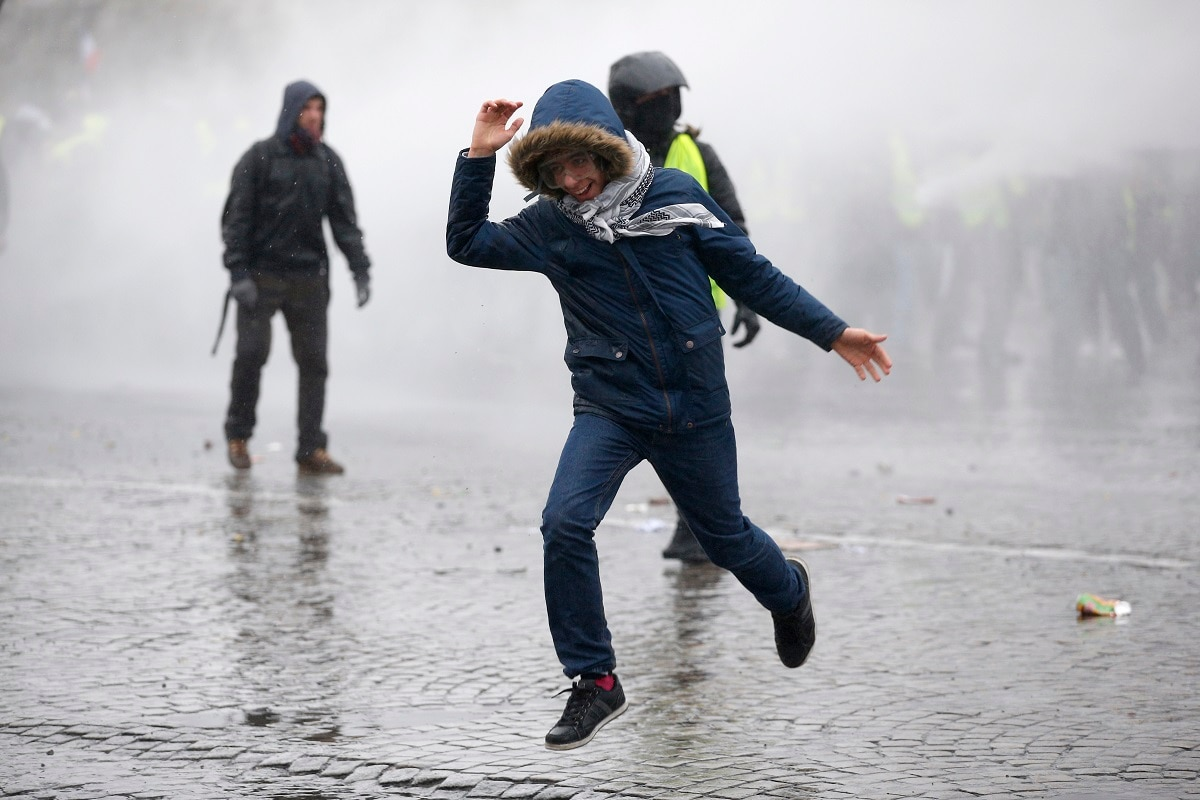 A demonstrator runs away after being sprayed with a water canon in clouds of teargas as yellow vest protesters clash with riot police on the famed Champs Elysees avenue in Paris. (AP Photo/Thibault Camus)