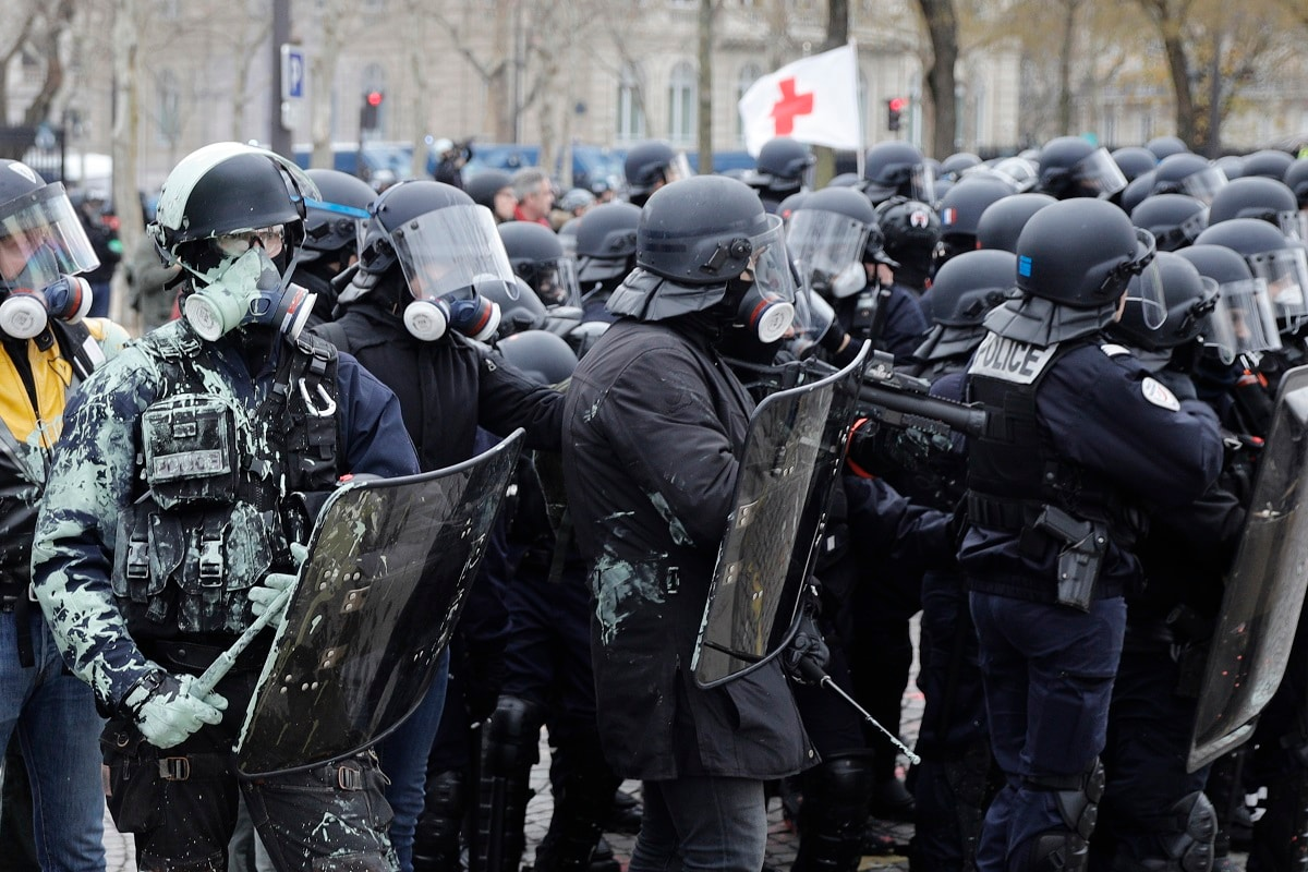 Riot police take position during clashes yellow vest protesters clash around the Arc of Triomphe in Paris. (AP Photo/Kamil Zihnioglu)