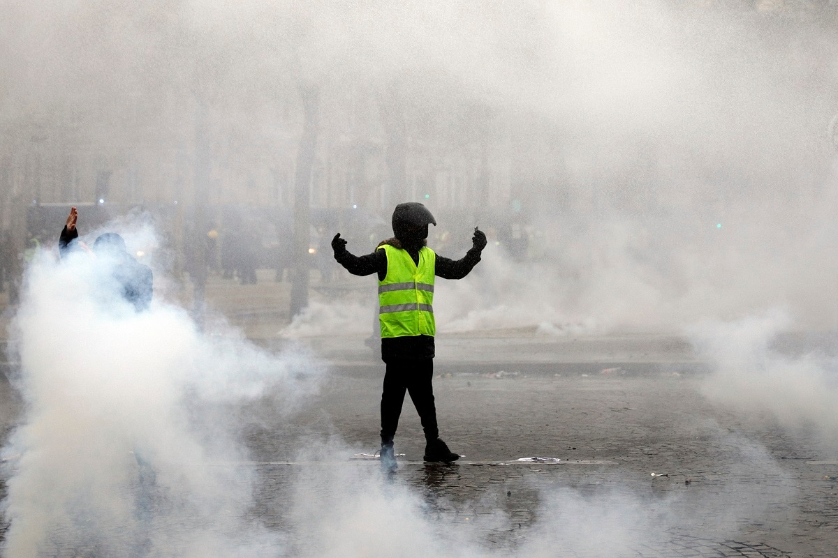 A yellow vest protester taunts riot police during clashes around the Arc of Triomphe in Paris. (AP Photo/Kamil Zihnioglu)