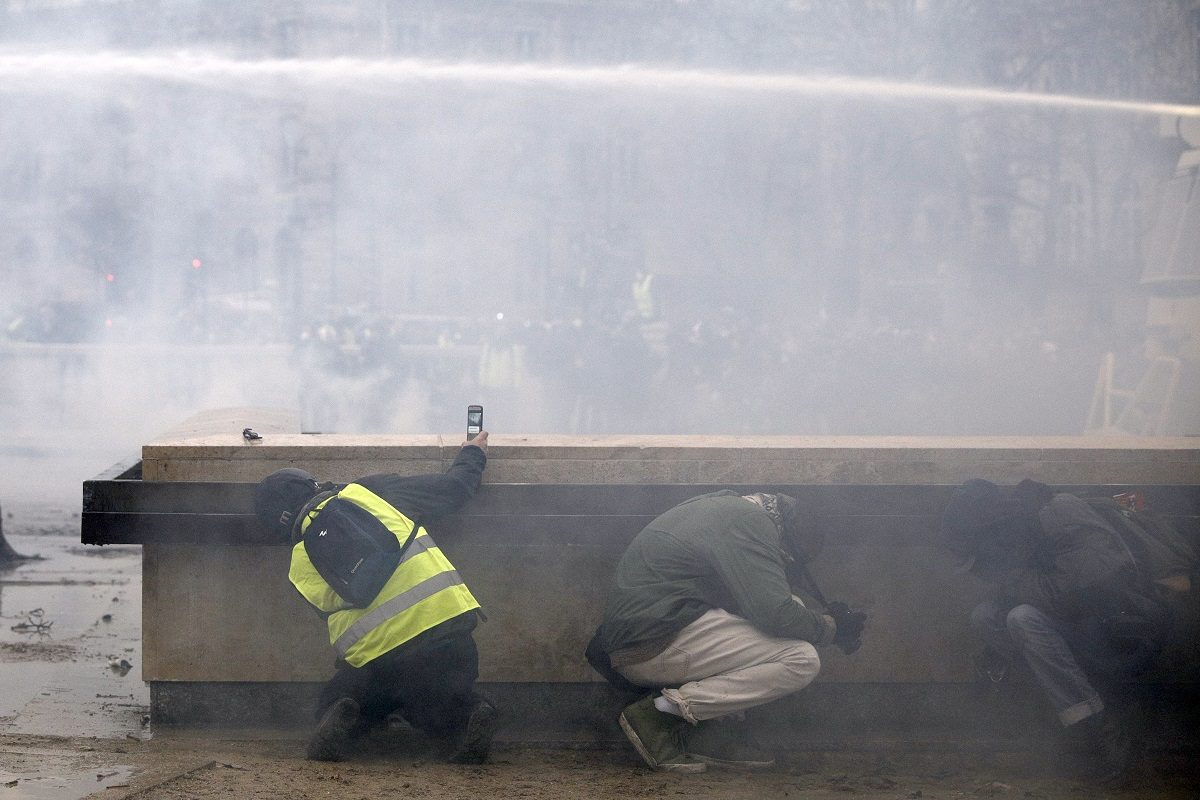 Yellow vest protesters take shelter as riot police use a water canon during clashes around the Arc of Triomphe, in Paris. (AP Photo/Kamil Zihnioglu)