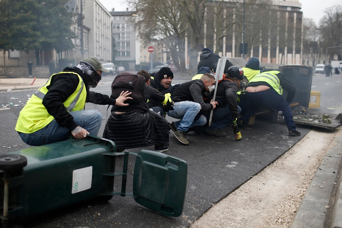 Yellow vest demonstrators take cover during clashes with French riot police during a demonstration in Bourges. (AP Photo/Rafael Yaghobzadeh)