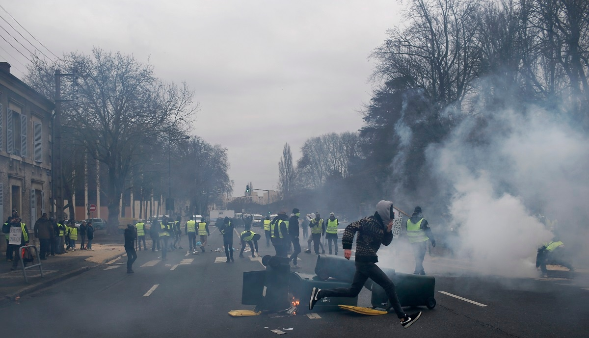 Yellow vest protestors set up barricades during a demonstration in Bourges. (AP Photo/Rafael Yaghobzadeh)