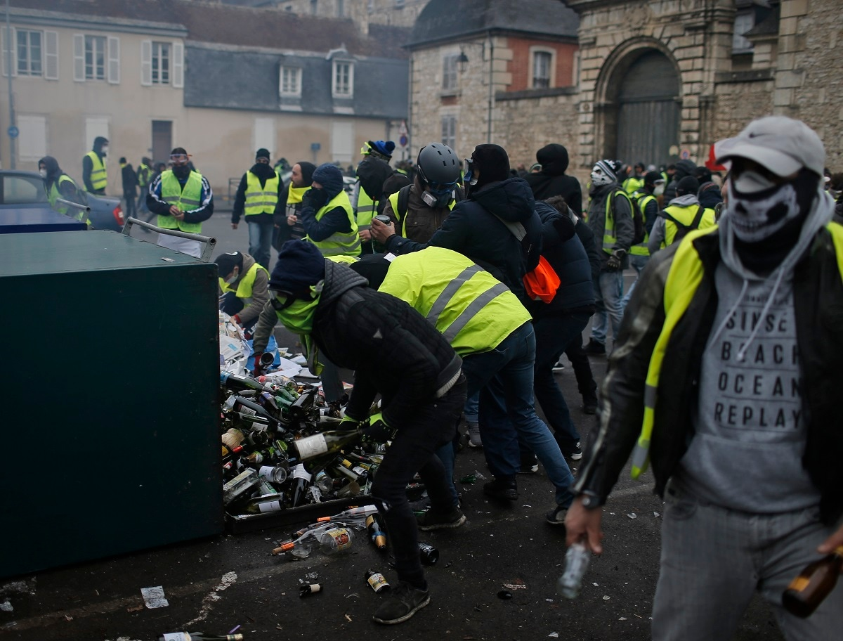 Yellow vest protestors break open a glass recycling container to arm themselves with glass bottles during clashes in Bourges. (AP Photo/Rafael Yaghobzadeh)