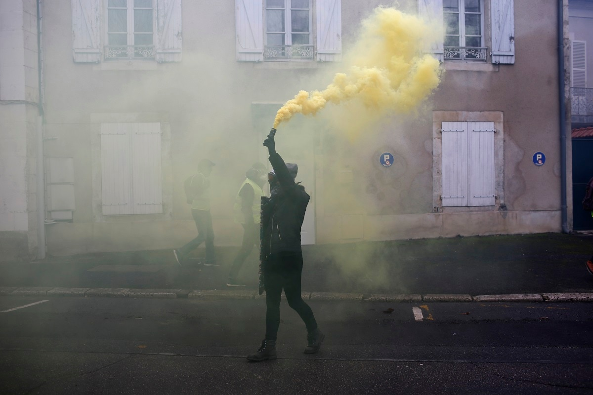 A protestor hold a smoke grande during a demonstration in Bourges. (AP Photo/Rafael Yaghobzadeh)