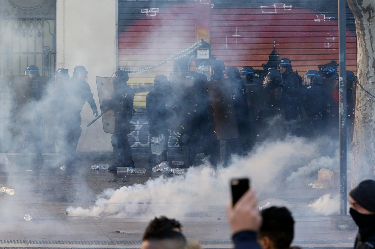 French riot police advances in a cloud of tear gas during a demonstration in Marseille, southern France. (AP Photo/Claude Paris)