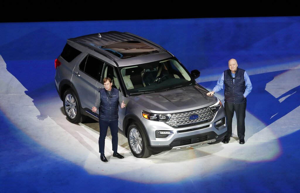 In this Wednesday, January 9, 2019 photo, Ford Motor Co., President, Global Markets Jim Farley, left, and President and CEO Jim Hackett stand next to the redesigned 2020 Ford Explorer during its unveiling, in Detroit. SUVs and a big pickup truck will get top billing at Detroit's auto show this year, but there are some surprise sports cars and electric vehicles on the agenda. The most popular vehicle of the bunch is the Ford Explorer, revealed ahead of the show Wednesday night at Ford Field, the home of the National Football League's Detroit Lions. (AP Photo/Carlos Osorio, File)
