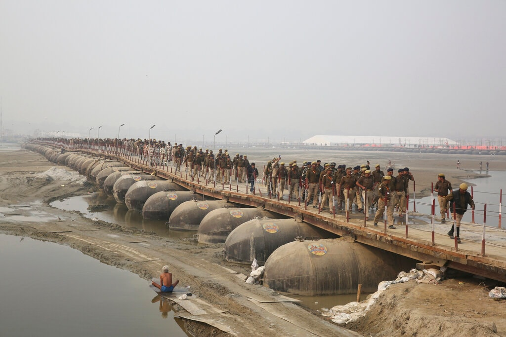 Indian police personnel march through a pontoon bridge at Sangam, the confluence of rivers Ganges and Yamuna as part of security arrangements for the Kumbh Festival in Allahabad, india, Sunday, January 13, 2019. (AP Photo/Rajesh Kumar Singh)
