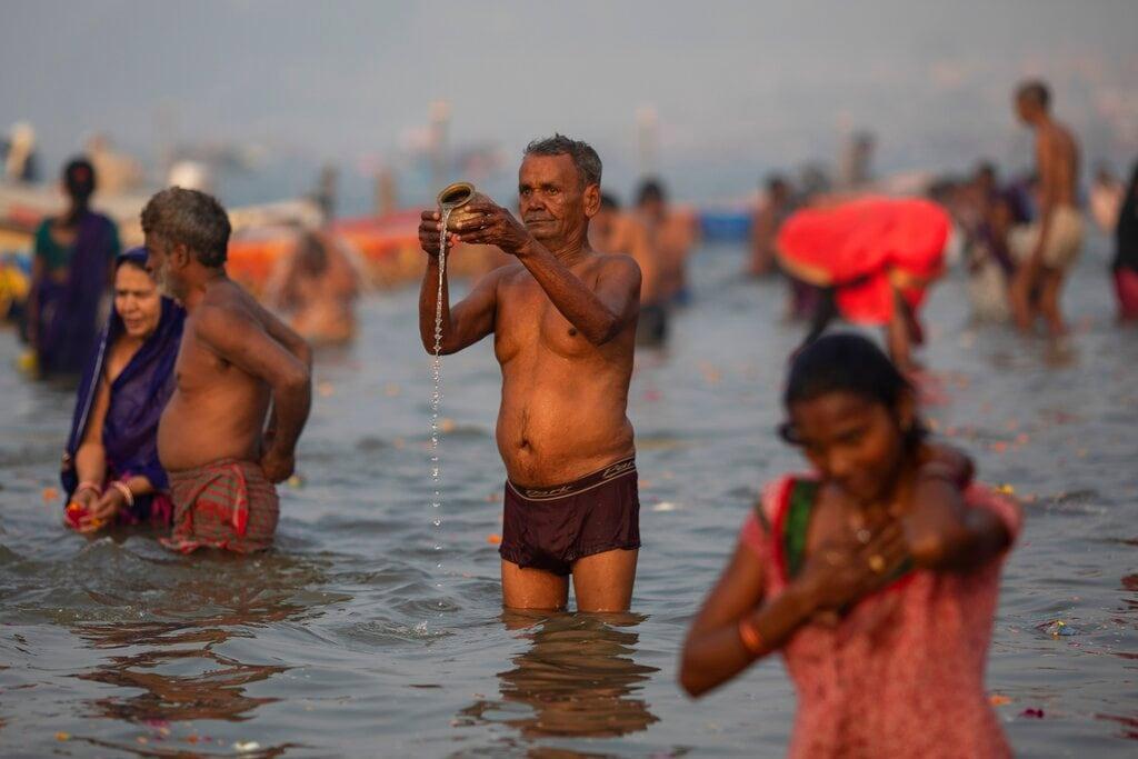 A Hindu pilgrim prays at Sangam, the confluence of the rivers Ganges, Yamuna and mythical Saraswati, during the Kumbh Mela festival in Allahabad, India, Monday, January 14, 2019. (AP Photo/Bernat Armangue)
