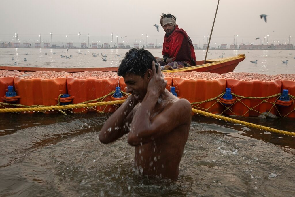 A Hindu devotee takes a holy dip at Sangam, the confluence of the rivers Ganges, Yamuna and mythical Saraswati, during the Kumbh Mela festival in Allahabad, India, Monday, January 14, 2019. (AP Photo/Bernat Armangue)