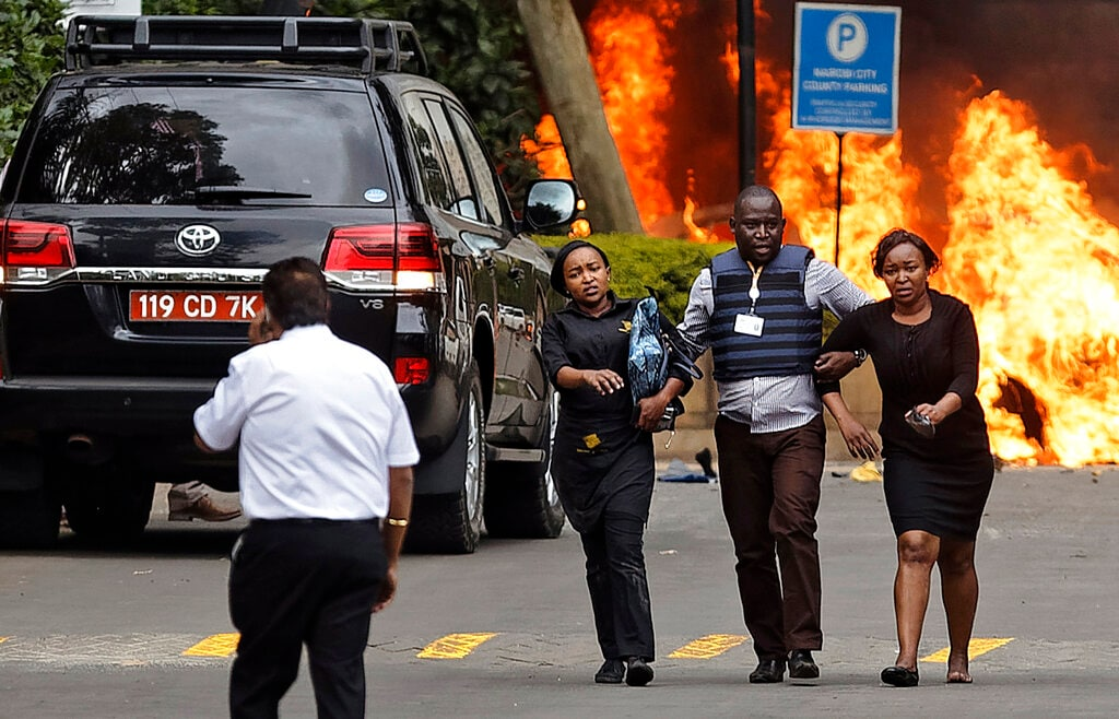 Security forces help civilians flee the scene as cars burn behind, at a hotel complex in Nairobi, Kenya Tuesday, Jan. 15, 2019. Terrorists attacked an upscale hotel complex in Kenya's capital Tuesday, sending people fleeing in panic as explosions and heavy gunfire reverberated through the neighborhood.