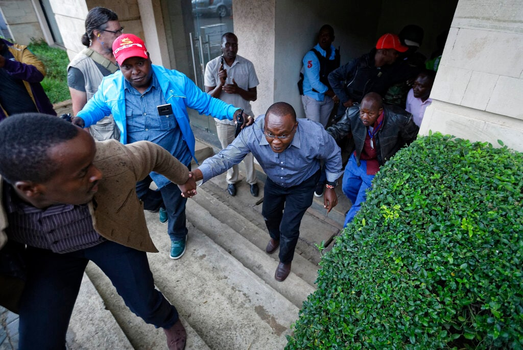 Civilians flee the scene at a hotel complex in Nairobi, Kenya Tuesday, Jan. 15, 2019. Terrorists attacked an upscale hotel complex in Kenya's capital Tuesday, sending people fleeing in panic as explosions and heavy gunfire reverberated through the neighborhood.
