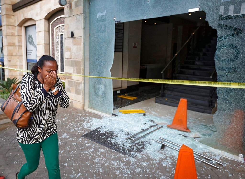 A woman reacts as she flees the scene at a hotel complex in Nairobi, Kenya Tuesday, Jan. 15, 2019. An upscale hotel complex in Kenya's capital came under attack on Tuesday, with a blast and heavy gunfire. The al-Shabab extremist group based in neighboring Somalia claimed responsibility and said its members were still fighting inside.