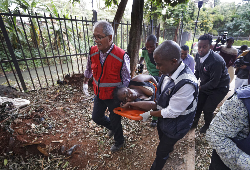 An injured woman is carried away by paramedics at a hotel complex in Nairobi, Kenya Tuesday, Jan. 15, 2019. Terrorists attacked an upscale hotel complex in Kenya's capital Tuesday, sending people fleeing in panic as explosions and heavy gunfire reverberated through the neighborhood.
