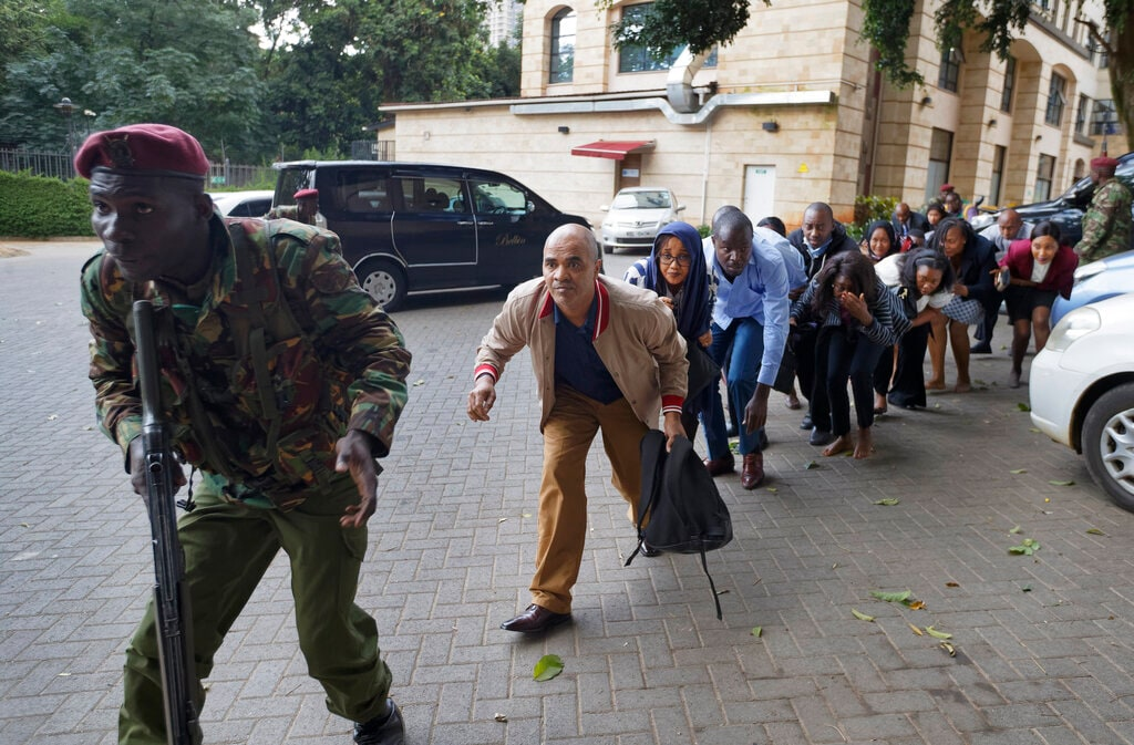 Civilians who had been hiding in buildings flee under the direction of a member of security forces at a hotel complex in Nairobi, Kenya Tuesday, Jan. 15, 2019. Terrorists attacked an upscale hotel complex in Kenya's capital Tuesday, sending people fleeing in panic as explosions and heavy gunfire reverberated through the neighborhood.