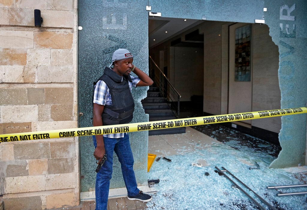 A plain-clothed member of security forces stands by the entrance to a hallway in which an unexploded grenade lies, at a hotel complex in Nairobi, Kenya Tuesday, Jan. 15, 2019. Terrorists attacked an upscale hotel complex in Kenya's capital Tuesday, sending people fleeing in panic as explosions and heavy gunfire reverberated through the neighborhood.