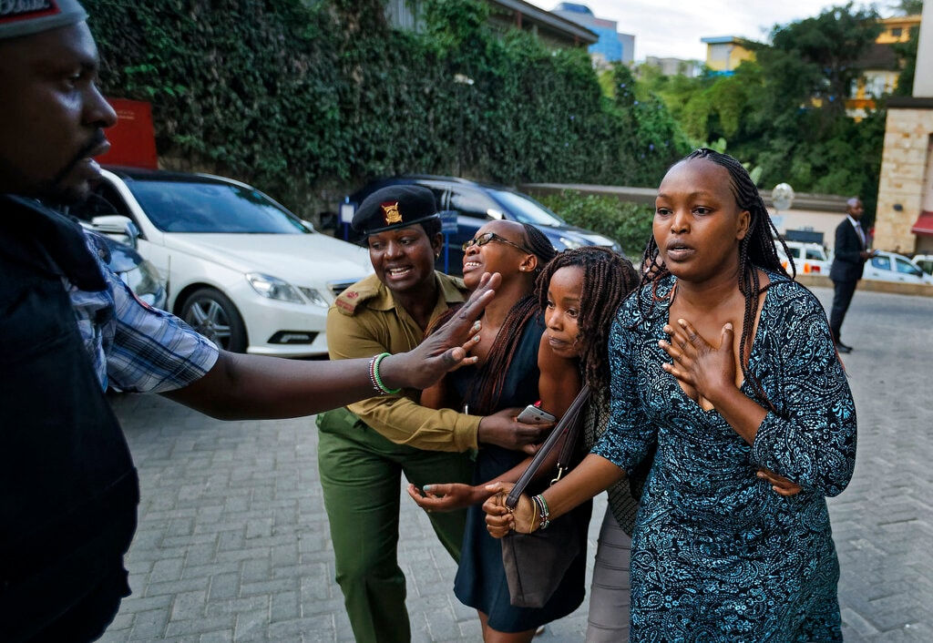 Civilians flee helped by a member of the security forces at a hotel complex in Nairobi, Kenya, Tuesday, Jan. 15, 2019. Terrorists attacked an upscale hotel complex in Kenya's capital Tuesday, sending people fleeing in panic as explosions and heavy gunfire reverberated through the neighborhood.